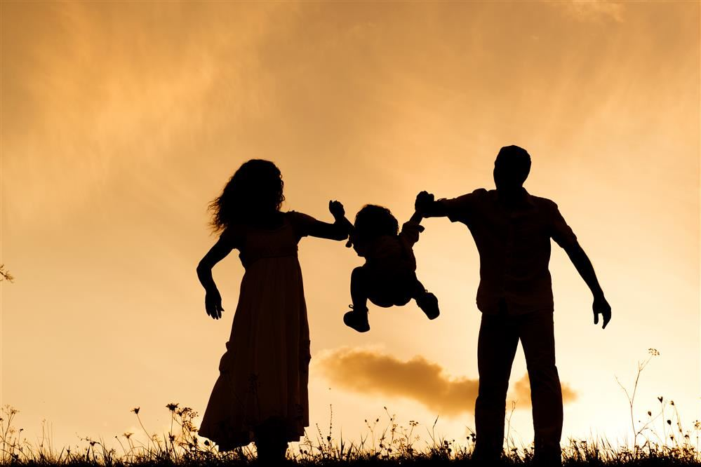 Silhouette of parents having fun with their child.