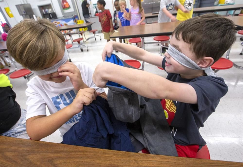 Two students working with blindfolds on